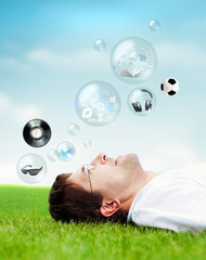 Adult man lying on grass and looking up. Dreaming. Different obj