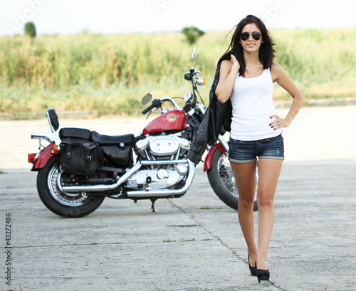 Young beautiful woman walking from a motorcycle