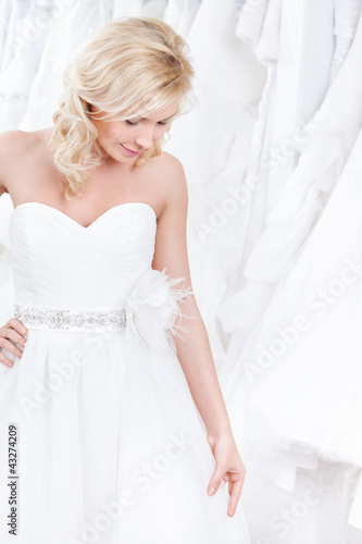 Youg girl is trying on a charming wedding gown, white background