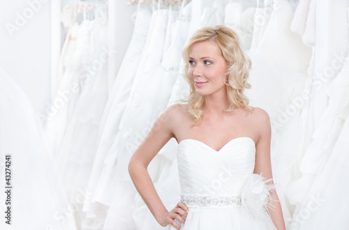 Youg girl is trying a beautiful wedding gown on