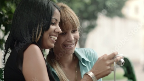 Happy young women looking at pictures on snapshot camera