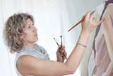 Woman artist draws a portrait of a woman. In the studio. poster