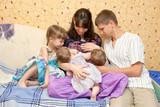 Breast feeding two little sisters twin girls. Big family