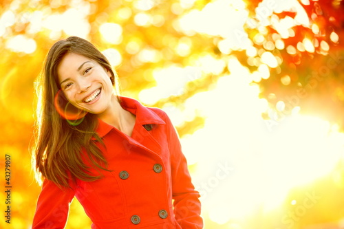 Autumn red trench coat woman in sunny tree leaves