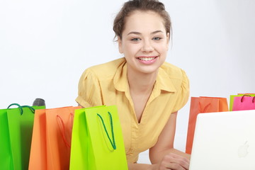 Woman surrounded by bags shopping on-line.