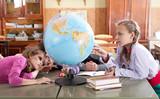 Schoolchildren exploring globe in classroom poster