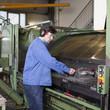 Arbeiter reinigt Maschine in Fabrik