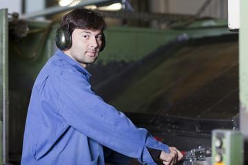 Arbeiter an Maschine in Fabrikhalle