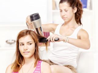 Teenage girl dries hair to her friends
