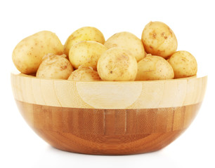 young potatoes in a wooden bowl isolated on white