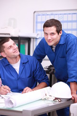Two factory workers in the office checking stock