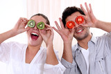 Couple holding fruit to their eyes