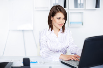 smiling business woman working on a laptop at office