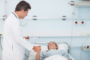 Doctor looking at his patient while holding her hand