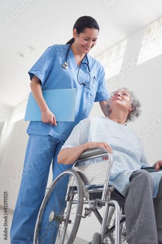 Elderly patient in a wheelchair next to a nurse