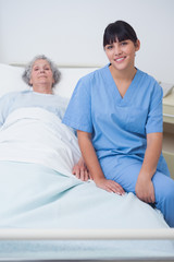 Nurse sitting on a medical bed