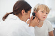 Doctor auscultating the ear of a child