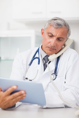 Doctor using a tablet computer while calling