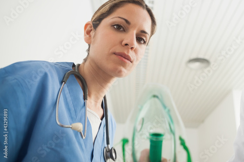 Nurse holding an oxygen mask while looking at camera