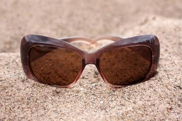 Sun glasses on a sand