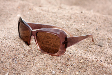 Sun glasses on a sand