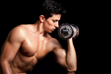 Handsome healthy man lifting weights on black background