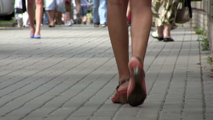 Naked female feet in the city and crowd