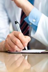 Closeup shot of a doctor writing a medical recipe