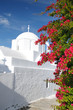 Greek orthodox church against blue sky with flowers