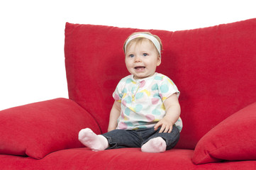 baby girl in a big red sofa