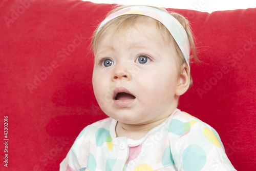 baby girl seated in a big red sofa.