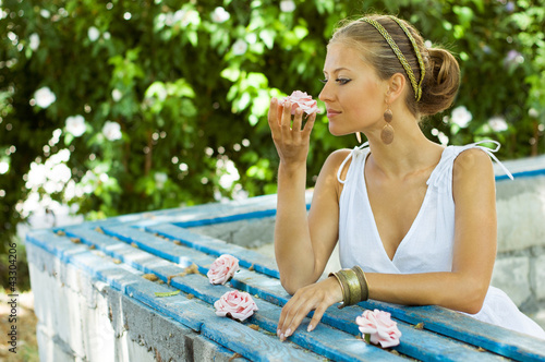 Greek styled girl smelling a rose
