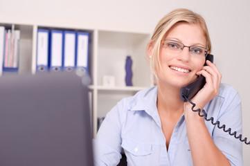 Attraktive blonde Frau telefoniert im Büro