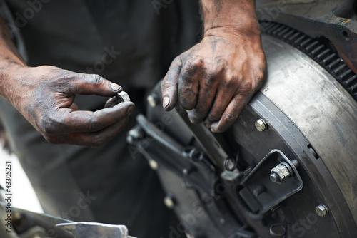 Leinwanddruck Bild auto mechanic hands at car repair work