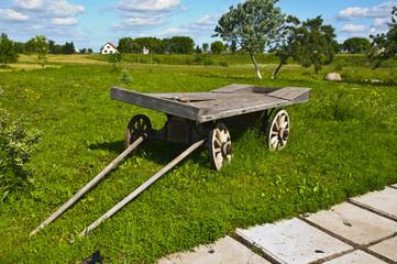Старая деревянная телега на фоне сельского пейзажа
