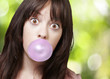 young girl with a pink bubble of chewing gum against a nature ba