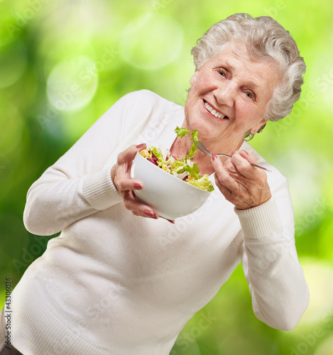 portrait of senior woman eating a fresh salad against a nature b