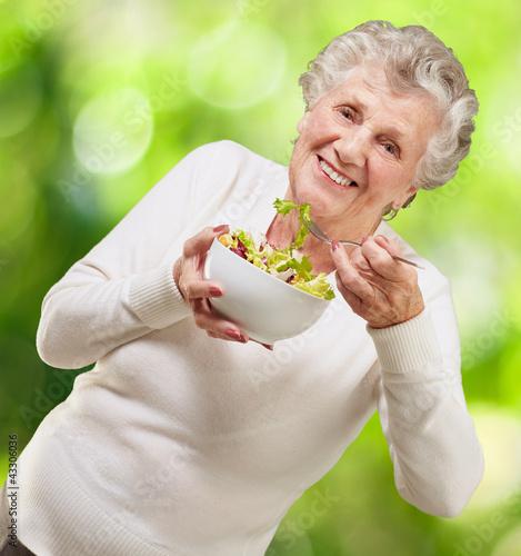 portrait of senior woman eating a fresh salad against a nature b