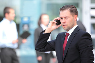 A young handsome business man on phone at office building