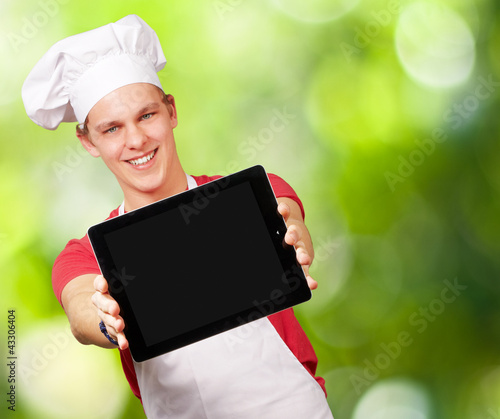 portrait of young cook man showing a digital tablet against a na