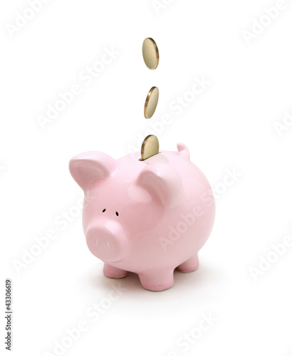 Golden coins falling into a piggy bank isolated on white