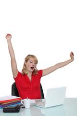 Woman yawning at a desk