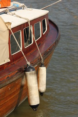 Wooden boat at harbor, with withe fenders