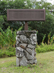 blank wooden sign on lava rock stand