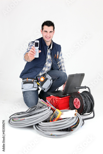 Happy electrician showing cellphone
