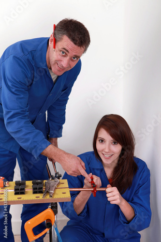 Plumber and assistant butting copper pipe