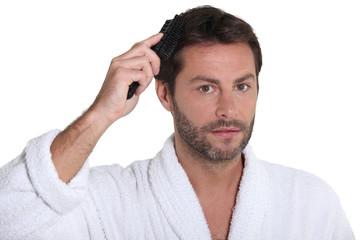 Man wearing a toweling robe brushing his hair
