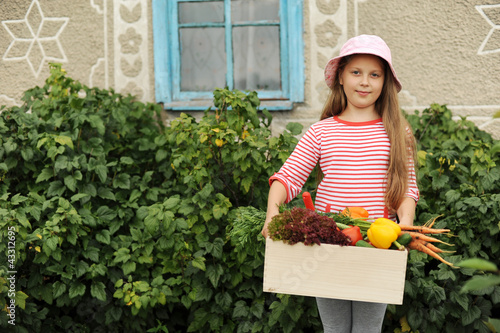 Girl with a box of vegetables