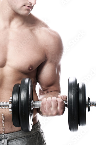 Muscular guy doing exercises with dumbbells