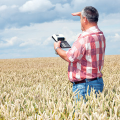 Farmer with computing machine in the field